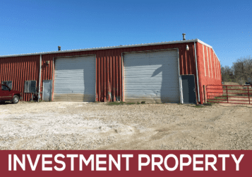 red metal investment property building with overhead doors for sale along Old Highway 10 in East Bismarck